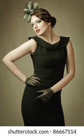 Young slim woman in black dress looks coquettishly