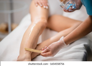 young slim woman came to get laser epilation procedure in salon. cropped female lie on bed while doctor applying moisturiser on legs before using ipl machine