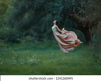 Young slim woman with dark hair and neat hair dressed long luxurious waving flying dress up into the air. iFreedom, to escape from slavery. Levitation, soaring, taking off. art photo