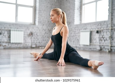 Young slim woman is doing some twine to stretch her legs. Joyful talented woman doing the splits