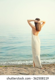 Young slim woman dressed in long white dress with open back, standing back with hands behind head, relaxed breathing ocean fresh air.