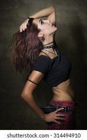 Young slim woman with gothic and heavy metal style and spiked collar posing on dirty wall background