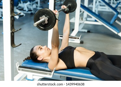 Young slim woman in a gym perfoms exercises with a barbell on a trainer bench. Healthy lifestyle concept