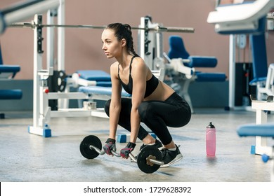 Young slim woman in a gym perfoms squats exercises with a barbell. Healthy lifestyle concept