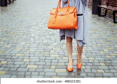 Young slim woman in high heels and gray knitted long dress with large bright orange leather bag in hand in the park. Autumn street fashion look, business clothes