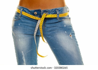 a young, slim woman in jeans with tape measure after a successful diet
