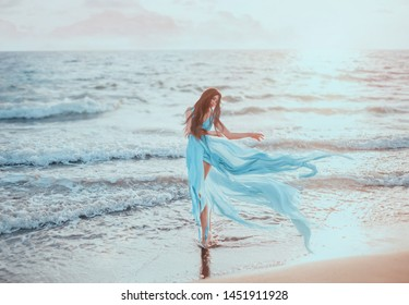 Young, slim woman with long legs dancing on the ocean, hair and blue dress fluttering in the wind. Sea with waves, a beautiful sunset. Glamorous lady vintage style. Happy travel leisure holiday
