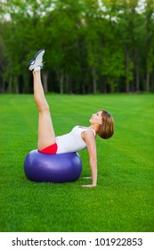 Young slim woman making exercises on fitball, outdoor