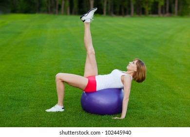 Young slim woman making exercises on fit ball, outdoor