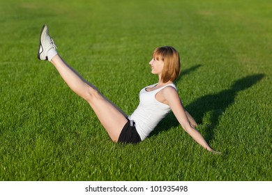 Young slim woman making fitness exercises, outdoor