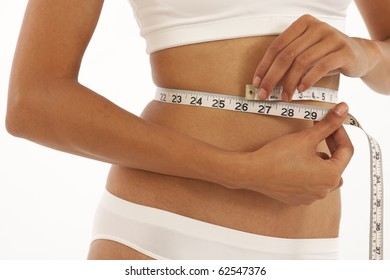 Young slim woman measuring her stomach with measuring tape