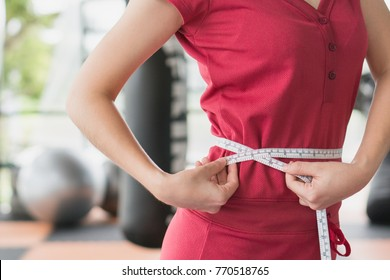 Young slim woman measuring her waist by measure tape after a diet with accessory in sporty gym as background.