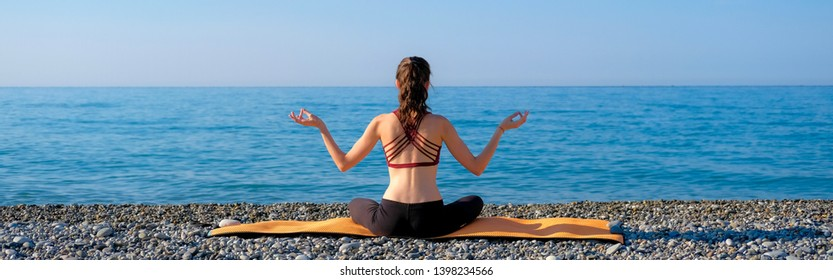 Young slim woman meditating on orange yoga mat back view outdoors at pebble beach by the sea. Yoga at nature concept.