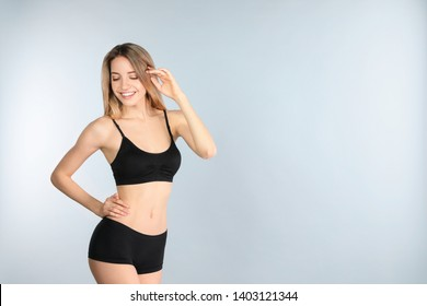 Young slim woman on light background, space for text. Perfect body