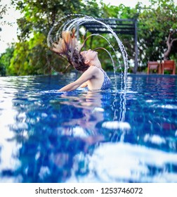Young slim woman in an outdoor pool with flying hair, spray beauty freedom youthful rest