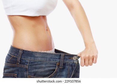 Young slim woman in oversized pair of jeans.  Isolated on the white background