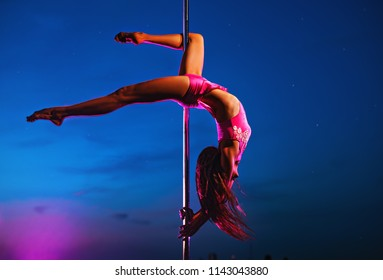 Young slim woman pole dancing at night on dark blue sky background