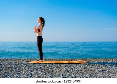 Young slim woman practicing on orange yoga mat outdoors at pebble beach by the sea. Yoga at nature concept. Girl standing with prayer hands.