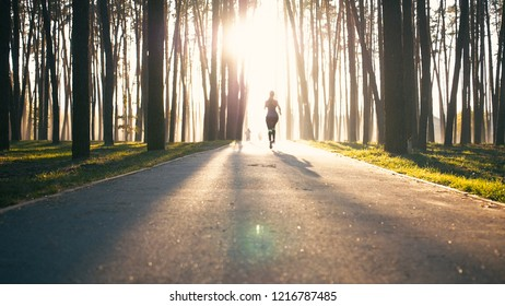 Young and slim woman run. Girl is jogging very fast. She dissapears in lights of morning sun.