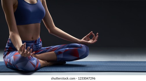 Young slim woman sitting in meditation pose on yoga mat. Charming light and tranquil atmosphere. Dark background, copy space.