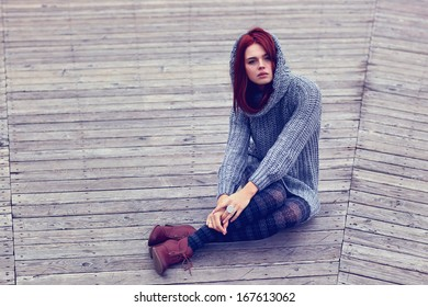 Young slim woman sitting outdoors.