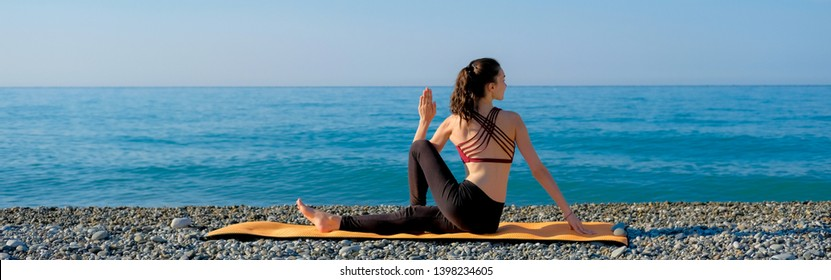 Young slim woman sitting spinal twist on orange yoga mat, practicing outdoors at pebble beach by the sea. Yoga at nature concept.
