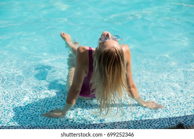 Young slim woman in a swimming pool resting and enjoying summer holidays