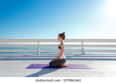 Young slim woman in tight sportswear sitting on purple yoga mat and practicing outdoors at white wooden seafront.
