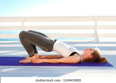 Young slim woman in tight sportswear practicing yoga outdoors at white wooden seafront. Pelvic lift exercise.