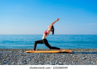 Young slim woman in tight sportswear standing in warrior pose 1 on orange yoga mat outdoors at pebble beach by the sea. Yoga at nature concept.