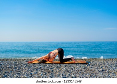 Young slim woman in tight sportswear doing thread the needle pose on orange yoga mat outdoors at pebble beach by the sea. Yoga at nature concept.