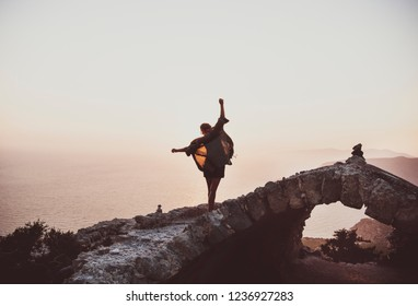 Young slim woman tourist balancing on stones of Monolithos castle in Rhodes island, Greece, at sunset on clear summer day. Freedom, open mindless, lifestyle concept