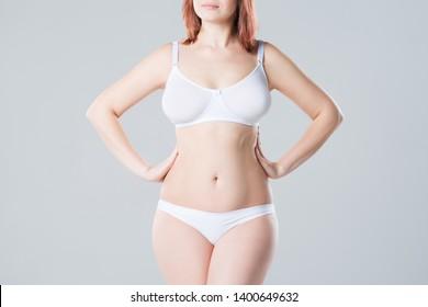 Young slim woman in underwear on grey background, beautiful female body, studio shot