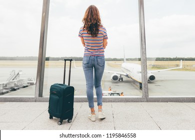 Young slim woman waiting her flight in lounge hall (just after duty free) in airport with her hand luggage (green trolley). Lost or canceled flight, need compensation concept. Eindhoven, Netherlands