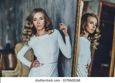 Young slim woman in white dress standing at mirror. Vintage film style colors.