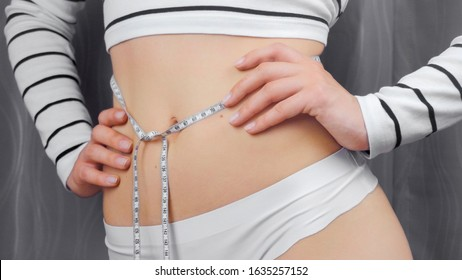 Young slim woman in white underwear measuring her waist. A woman measures her waist with a centimeter tape. Advocacy for proper nutrition and a healthy lifestyle. Diet and sports