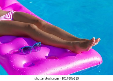 Young slim woman's legs on an air mattress in the swimming pool