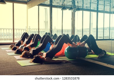 Young slim women in black sportswear lying on fitness mats and do exercise with help fitball in fitness gym with reflection in mirror against panoramic windows with bright sun light