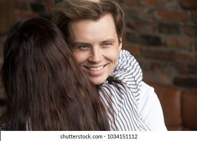 Young sly liar man happily smiling while woman embracing him, dishonest cheating boyfriend womanizer hiding grin hugging naive girlfriend, insincere husband deceiving wife showing fake feelings