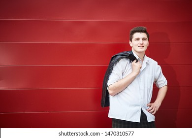 A young smailing man in a white shirt stands against a bright red wall.