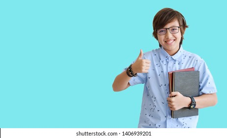young and smart boy in blue shirt and wearing glasses and showing thumb up symbol and happy smiling face with books on green background (education or success concept)