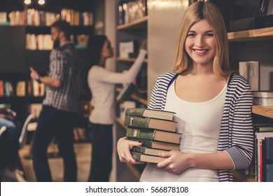 Young smart people are working hard in the modern library. Girl in the foreground is holding a pile of books, looking at camera and smiling