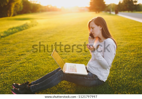 Young smart student female in casual clothes. Woman talking on mobile phone, working on laptop pc computer in city park on grass sunshine lawn outdoors. Mobile Office. Freelance business concept