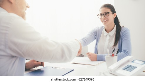 Young smart woman having a successful job interview, the examiner is shaking her hand