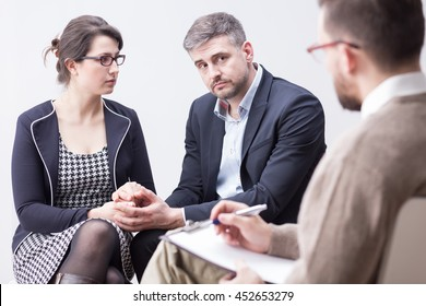 Young, smartly-dressed couple holding each other's hands during a therapy meeting