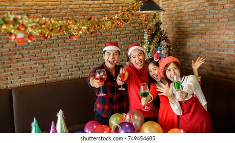 Young smile Asian men and women, 20 to 30 years old, with Santa  hats clink glasses of red and green drinking wine or champagne for christmas or xmas and new year party by top view shot.