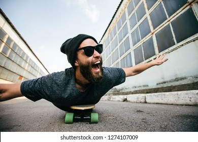 A young smile hipster lying rides longboard