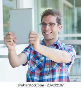 Young smiley male using tablet pc taking a selfie
