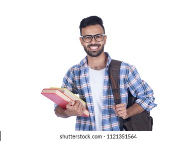 Young smiley student holding books carrying backpack, isolated on a white background.