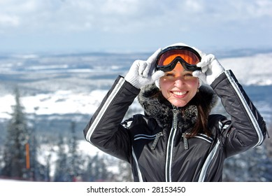 Young smiley woman in ski sunglasses over mountains landscape